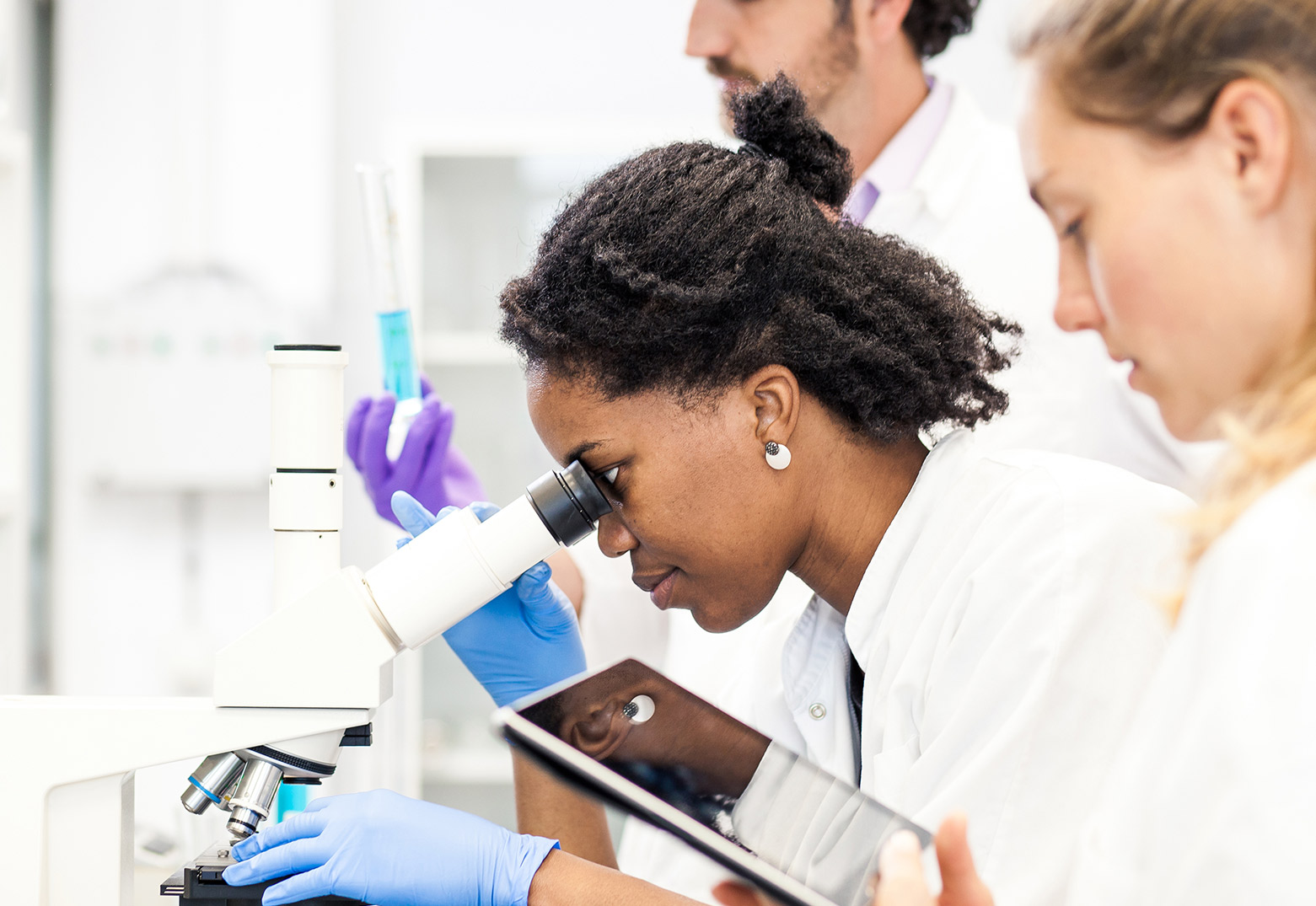 woman looking into microscope while co-worker looks at EHR