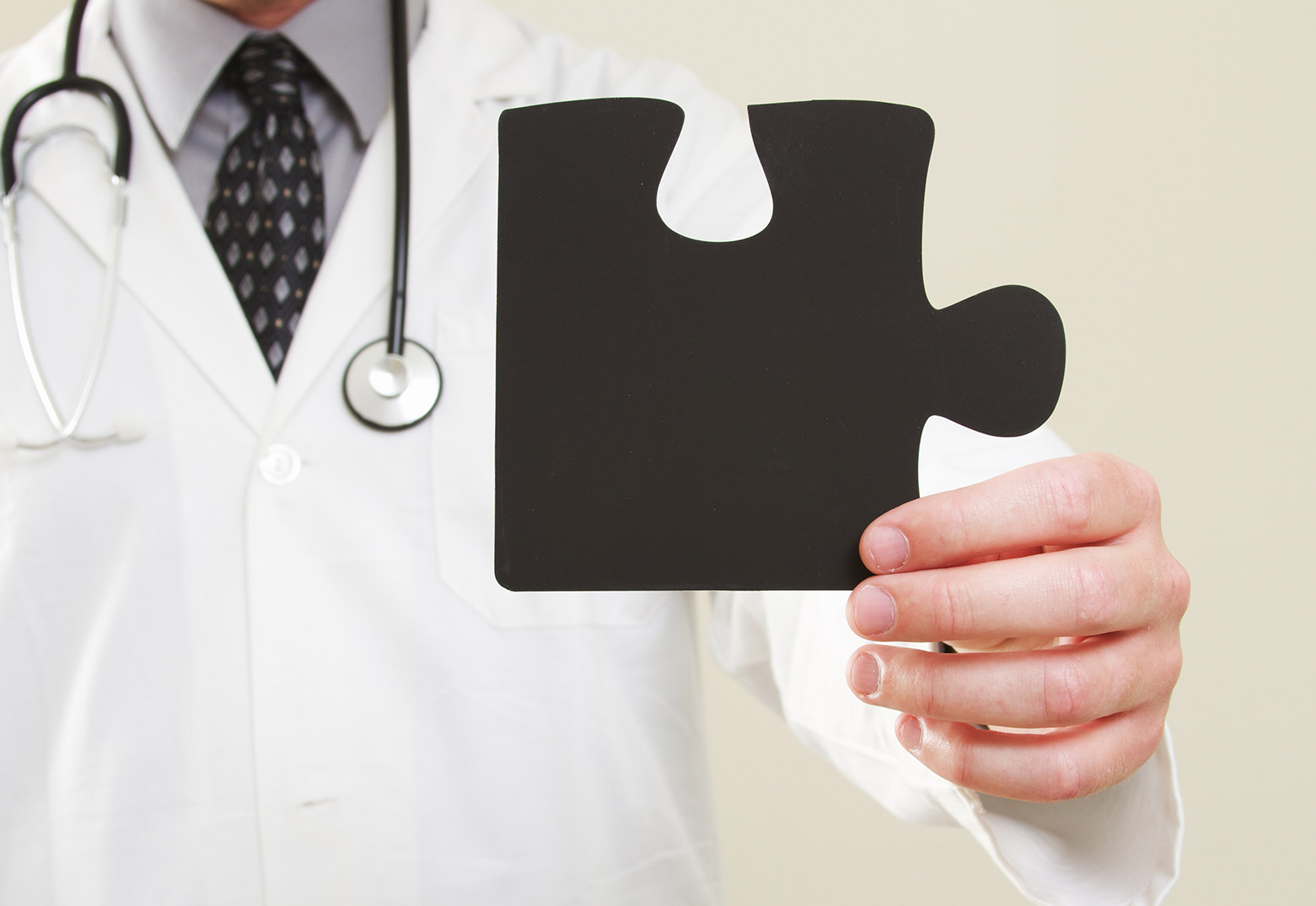 physician holding a missing piece of a puzzle representing a gap in care