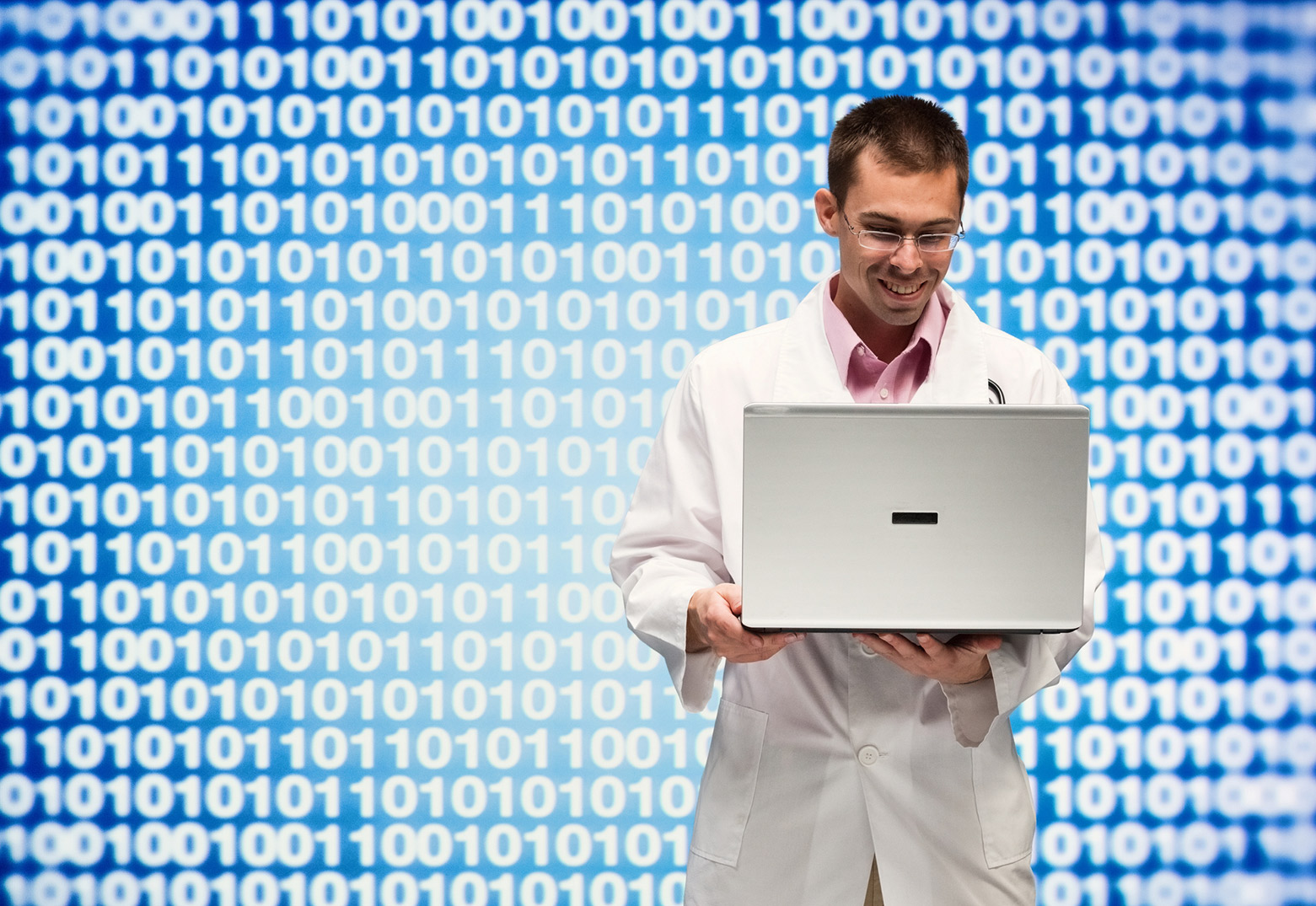 Doctor holding laptop with binary numbers in the background symbolizing data.