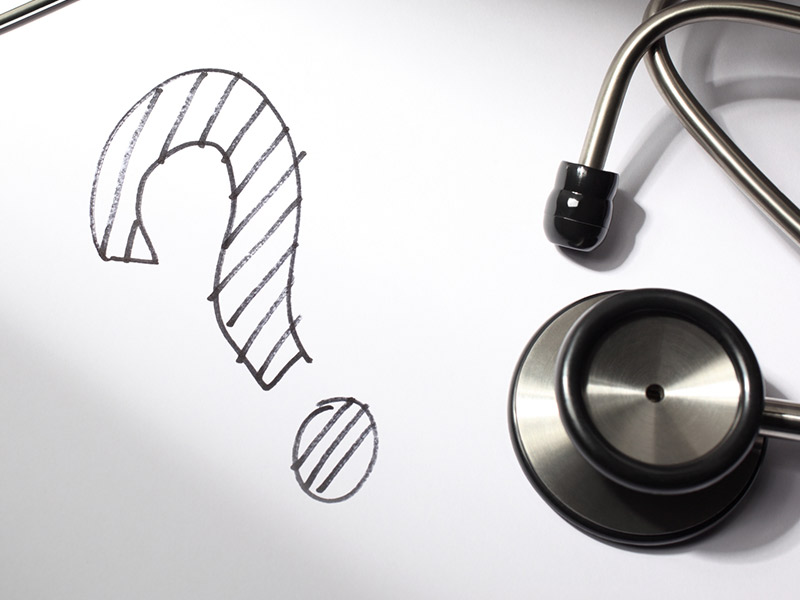 A question mark is drawn on a doctor's clipboard with stethoscope.