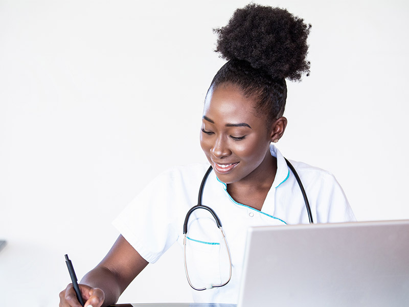 A young african american woman working in a doctor's office managing incoming referrals.